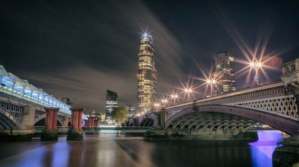 Blackfriars, London, UK. October 13, 2018.   Image shows a night scene looking over the River Thames in London, the street lights on Blackfriars bridge sparkle as the scene leads towards the tower with it's own guiding star atop