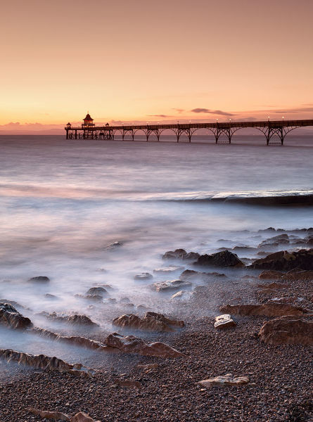 Cleveden pier, Somerset. August 28, 2011. Image shows a pier at sunrise with the tide in motion, light clouds low on the horizon in a golden sky