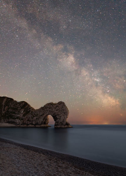 Durdle Dor, Dorset, UK. June 18, 2017. Image shows astro photography image of the well known UK landmark of Durdle Dor, behind is a starry night sky with the arc of the Milky Way cutting through