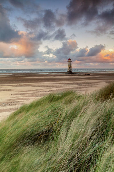 Image shows Talacre Lighthouse at low tide. Dramatic clouds scatter the sky the sun breaking through low on the horizon. Lines of sand caught by the morning breeze