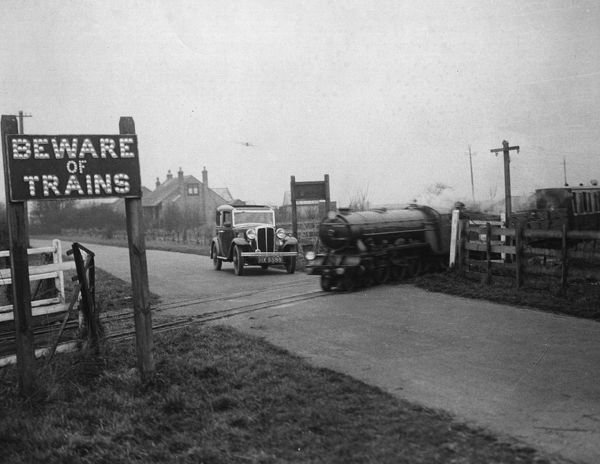 January 1933: The Romney Hythe and Dymchurch Light Railway, the smallest public railway in the world, still poses a danger to traffic at a level crossing. (Photo by Fox Photos/Getty Images)