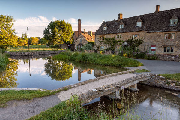 Cotswold, United Kingdom. July 07, 2019.   Scene shows early morning in a quaint English country village. The old millhouse and cottages are reflected in the village stream. The dawn sunrise lights the rear of the millhouse and the trees