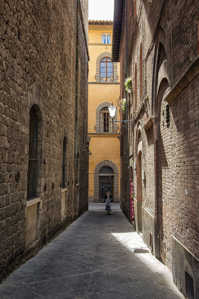 Small and narrow street of renaissance architecture in Italian city of Siena in Val d'Orcia,Tuscany,Italy