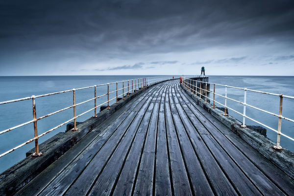 Whitby, Yorkshire, UK. August 19, 2018.   Image shows a brooding stormy scene of the pier in the seaside town of Whitby in North Yorkshire, England. The wooden planks of the pier, are weather worn and soaked with rain and seawater