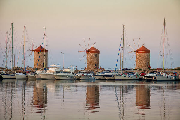 Sunset at the Mandraki Harbour and Old Windmills on greek island of Rhodos,Greece