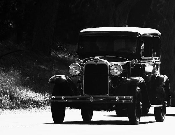 1931 Model A Ford. Black and White image of a 1931 Model A Ford driving down the Highway