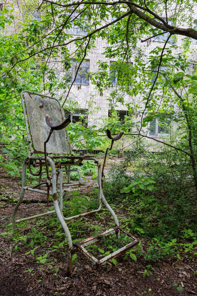 An old and rusty gynecologist abandoned in the middle of the forest in front of a decaying hospital building in the ghost city of Pripiyat