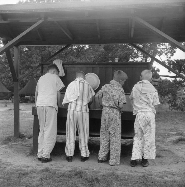 A group of young boys in their pyjamas at the washstand on summer camp at Camp Epworth, Jamespark, Long Island, New York