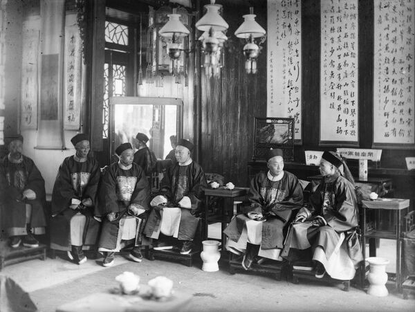 circa 1900: A meeting of Chinese men in a high-ceilinged room with wallhangings. (Photo by Hulton Archive/Getty Images)