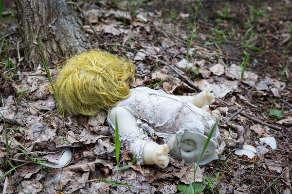 An abandoned broken baby doll in the middle of the forest inside the Chernobyl exclusion zone, near to the ghost city of Pripyat, Ukraine