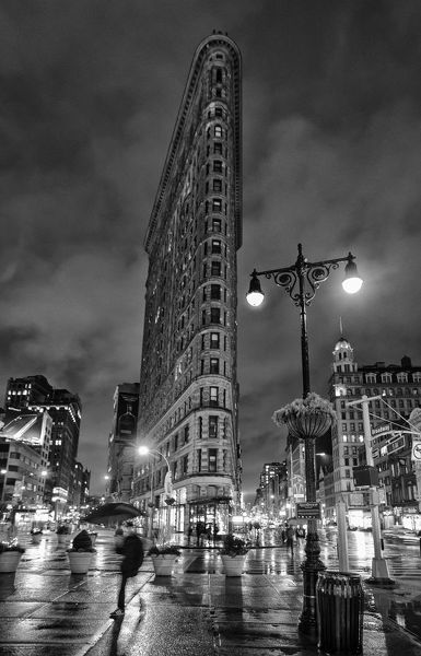 Downtown Manhattan street scene featuring the Flatiron Bldg with lights and traffic reflected on rainy streets in a time exposure photo (black and white image)