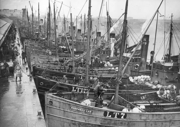 Drifters unload their fish at Lowestoft. With the Herring season in full swing the boats keep the steam up, as once unloaded they will immediately set out again