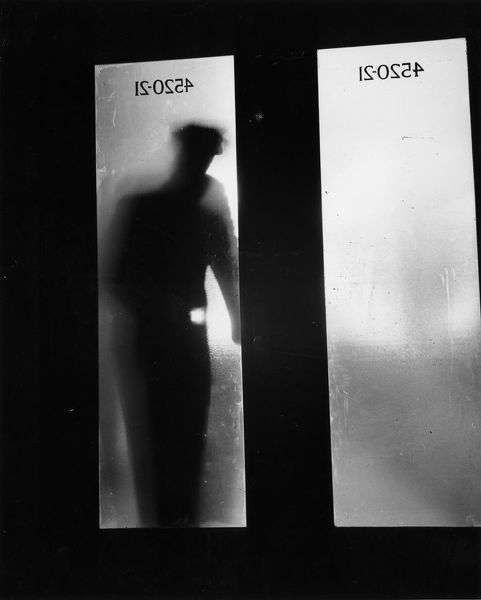 circa 1955: The silhouette of a policeman with a torch can be glimpsed through a textured glass door. (Photo by Three Lions/Getty Images)