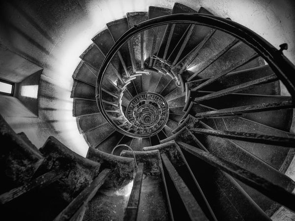 Monotone image of the staircase in The Monument to the Great Fire of London spiraling down. The handrail and the edges of the floors form two continuously line circling towards the center of the frame and drawing viewers' attention to the endless circles
