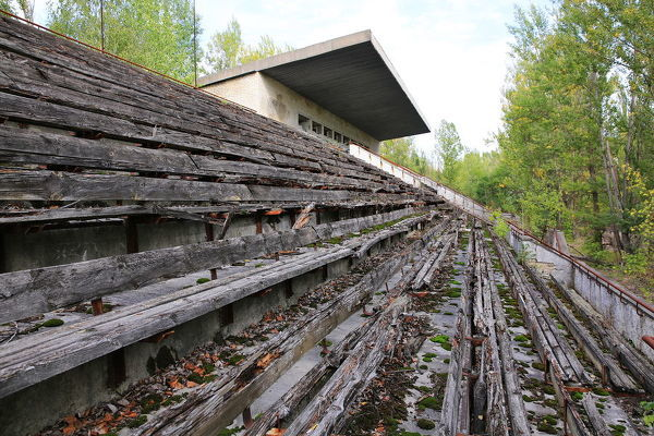 Empty stands of abandoned stadium in Pripyat city near Chernobyl  Rows of wooden benches on the deserted stands of dilapidated stadium