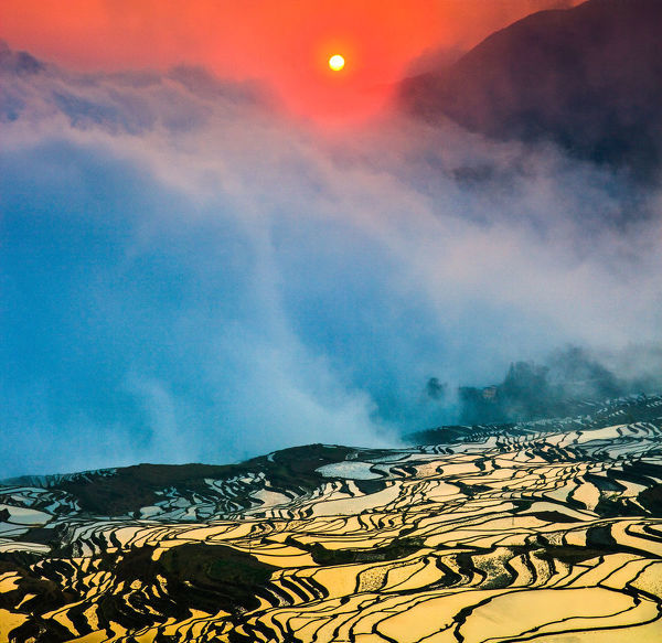 Sunrise over the terraced rice fields Ailao mountain in background, Yuanyang, China