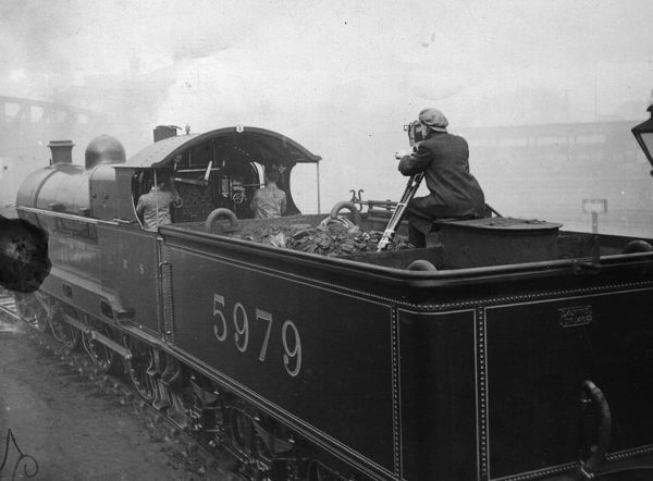 Train Filming. circa 1930: A cameraman filming the driver of an express train
