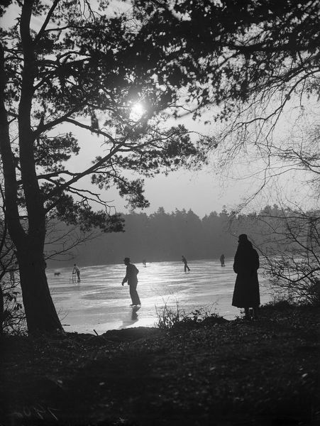 8th December 1933: A solitary figure comtemplates skaters on a frozen lake. (Photo by Fox Photos/Getty Images)