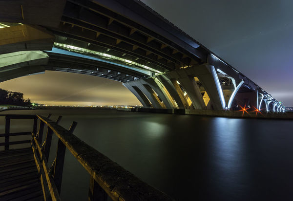 A long exposure picture of the Woodrow Wilson Bridge taken from the Virginia side of the Potomac River. The cloud cover is lit up on the left by Washington, DC and on the right by the Ferris Wheel at National Harbor