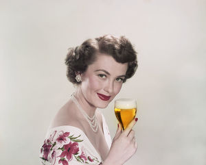 Young woman holding glass of beer, smiling, portrait