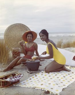 Young women holding hot dog on beach, smiling