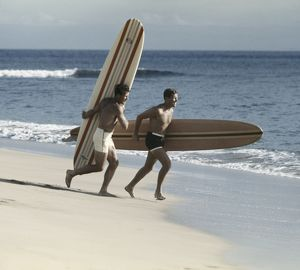 Young men running on beach with surfboard