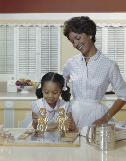 Mother and daughter with gingerbread biscuits, smiling