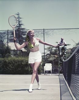 Young woman playing tennis, smiling