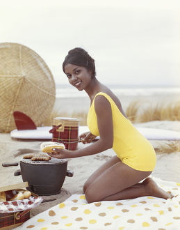 Young woman preparing hot dog on beach, smiling, portrait