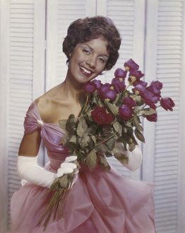 Young woman smiling and holding bunch of flowers, portrait