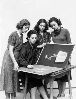3 young women observe a fourth draw artwork in portfolio.