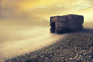 Abandoned bunker on the beach at sunrise