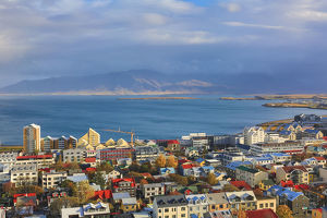 Aerial view over downtown Reykjavik with ocean and mountain at back, Iceland