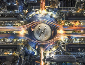 aerial top view traffic circle with speed light in city at night , Democracy Monument