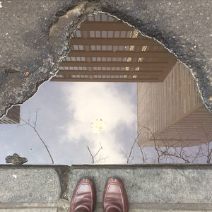 High Angle View Of Shoes Against Buildings Reflecting In Puddle