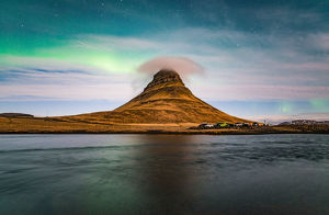 Aurora borealis and cloud cap over the Kirkjufell mountain the iconic landmark of