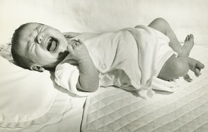 Baby boy (6-12 months) lying down on bed, crying, (B&W)