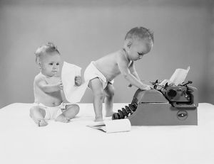 Baby standing at typewriter, twin seated behind looking at papers.