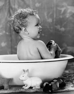 Baby with wet hair sitting in wash basin, smiling, taking a bath.