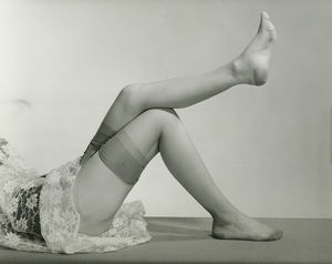 Woman wearing underskirt and stockings lying on floor, (B&W), low section