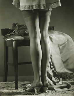 Woman in stockings standing indoors, (B&W), low section