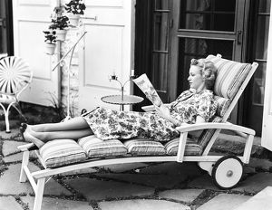 Blonde woman reading magazine on chaise lounge.