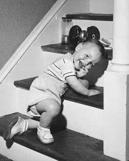 Boy (18-24 months) kneeling on steps, smiling, (B&W)