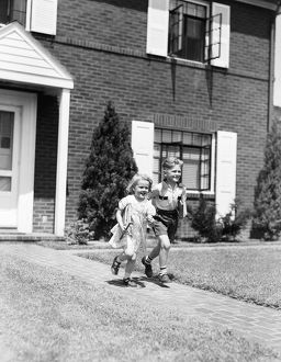 Boy and girl running down sidewalk, holding school books, going to school.