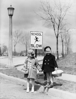 Boy and girl walking to school, about cross street by 'slow school' sign.