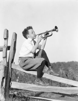 Boy sitting on fence, playing musical instrument.
