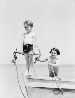 Boy standing on bow of row boat holding anchor, girl holding rope.