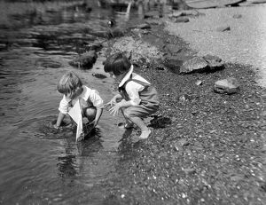 Two boys playing at water's edge with toy sailboat.