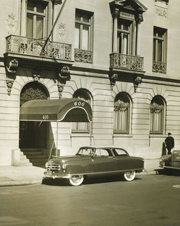 Car standing in front of hotel entrance, (B&W)