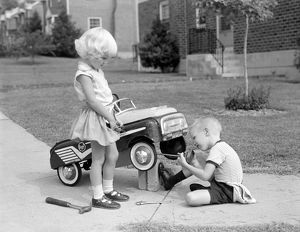 Children on suburban sidewalk, boy playing as mechanic, oiling toy pedal car.